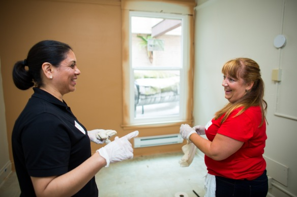 Volunteers Kathi Amis, left, and Karen Anderson, who both work in Key Private Bank's wealth management and nonprofit services, share a laugh while cleaning a room in the Kasota building. (Photo by Dan DeLong)