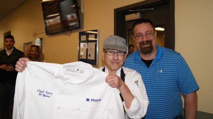 Chef Terry holding his new custom chef's coat highlighting his 20 years of service, with Director of Food Programs Brent Herrmann (right).